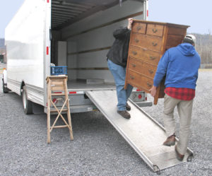 Two people moving furniture into a moving truck